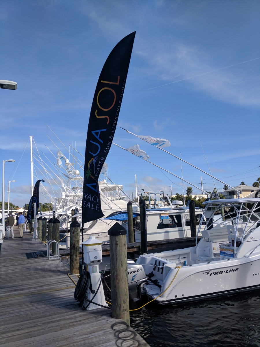 Boats at boat show with Aqua Sol Yacht Sales flag